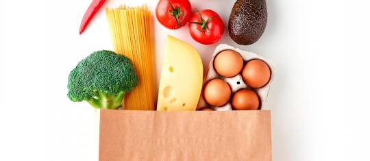 Paper grocery bag with vegetables, pasta, eggs and cheese top view isolated on white background