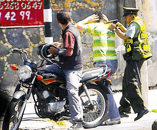 Un fotógrafo captó el momento preciso, en el cual el policía detuvo a unos de los asaltantes.