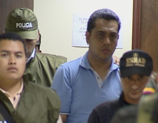 El de camisa azul es el ex oficial Manrique, durante un traslado a una audiencia.