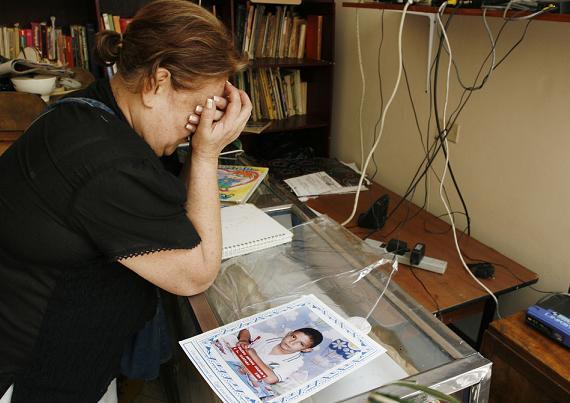 La abuela del pequeño Carlos llora ante su foto, en el escritorio del cual los ladrones asesinos sacaron los computadores. Foto de Esteban Vanegas.