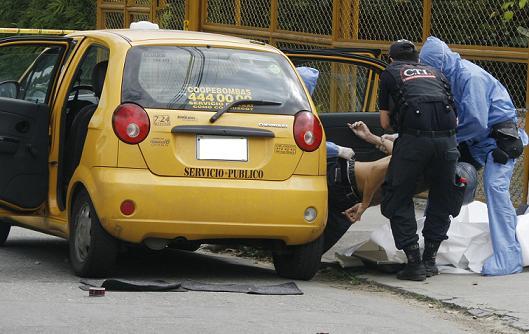Este fue el momento en el cual los criminalistas extrajeron el cadáver del taxi. Fotos de Esteban Vanegas.
