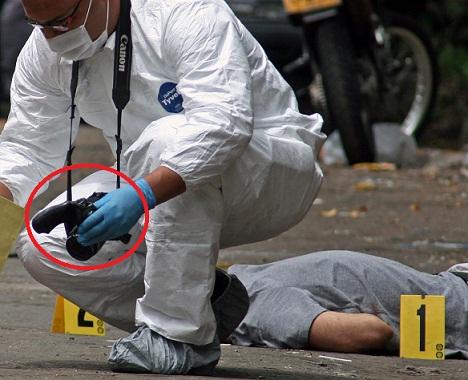 Esta es la escena del crimen en el barrio Guayabal. El criminalista sostiene el revólver incautado al supuesto ladrón. Foto de Carlos Taborda.
