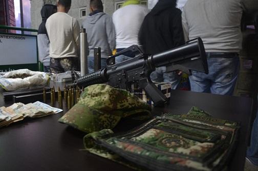 Los capturados junto al fusil Colt 9 milímetros con silenciador. Foto Policía Metropolitana.