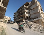 Syrian men ride a motorcycle past heavily-damaged buildings in the rebel-held town of Maaret al-Numan, in the north of Idlib province on September 27, 2018. OMAR HAJ KADOUR / AFP