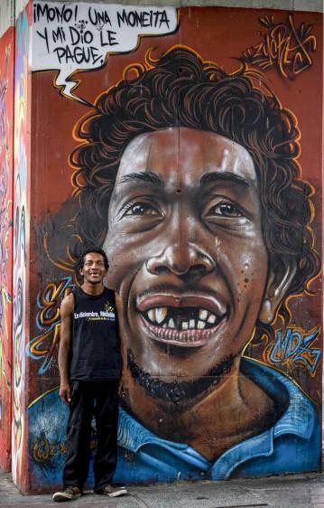 Sergio Andrés Posada posa frente al dibujo de su retrato, en el barrio Sevilla de Medellín. Foto: Jaime Pérez Munévar