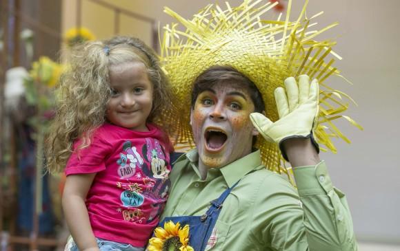 Pepe el espantapájaros posando con una niña en el Parque Comercial El Tesoro. FOTO CORTESÍA