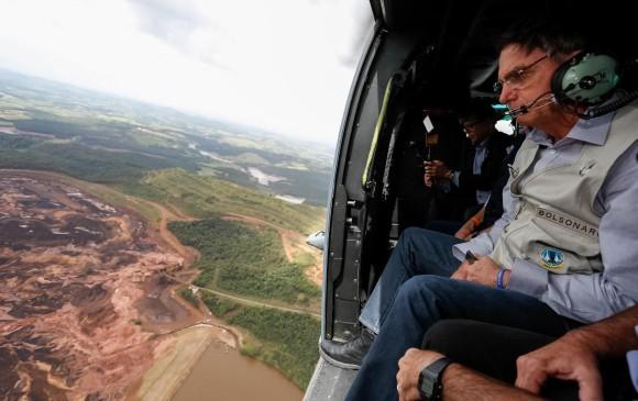 En la foto cedida por la presidencia de Brasil se observa al mandatario, Jair Bolsonaro mientras sobrevuela la zona afectada por una avalancha tras la rotura de una represa minera. Foto: EFE.