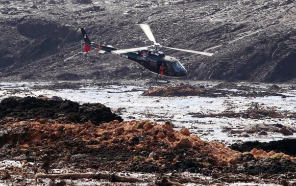 Un helicóptero busca sobrevivientes entre el río de lodo que cayó tras la ruptura de la represa. FOTO EFE