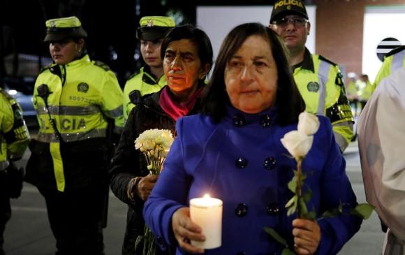 Ciudadanos y policías participan en un plantón este jueves frente a la Escuela de Cadetes de Policía General Francisco de Paula Santander, en Bogotá. FOTO EFE