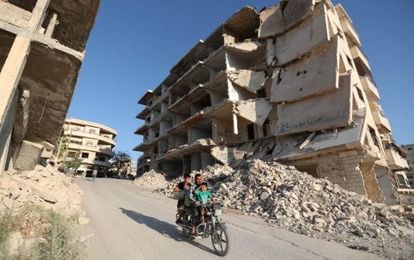 Syrian men ride a motorcycle past heavily-damaged buildings in the rebel-held town of Maaret al-Numan, in the north of Idlib province on September 27, 2018. OMAR HAJ KADOUR / AFP