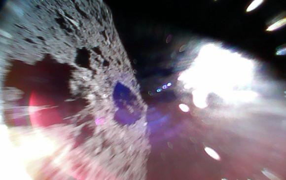 Imagen en color capturada mientras un explorador se mueve (durante un salto) en la superficie de Ryugu. La mitad izquierda de la imagen es la superficie del asteroide. La región blanca brillante es provocada por la luz solar. Foto: JAXA