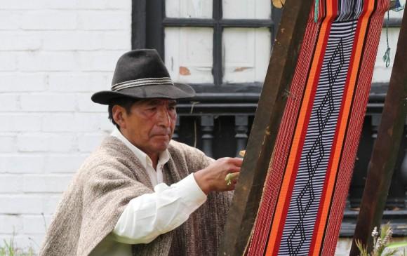 Otoniel Chenaz, tejiendo sobre un pilar vertical en Pasto, Nariño.