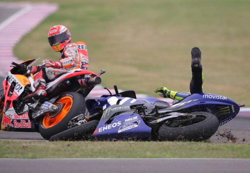 El piloto italiano de MotoGP Valentino Rossi (d), cae al piso en la última curva del circuito tras un toque con el piloto Marc Márquez, del equipo Repsol Honda Team.