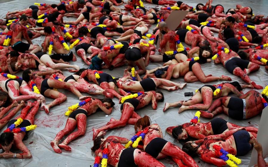 """Tendidos en el suelo, alrededor de 200 hombres y mujeres, que vestían únicamente un calzón negro, fueron rociados con tinta roja. En sus espaldas fueron acondicionadas banderillas con los colores de la bandera colombiana, para enfatizar en que el país """"no quiere que se haga un espectáculo de la muerte"""". FOTO REUTERS"""