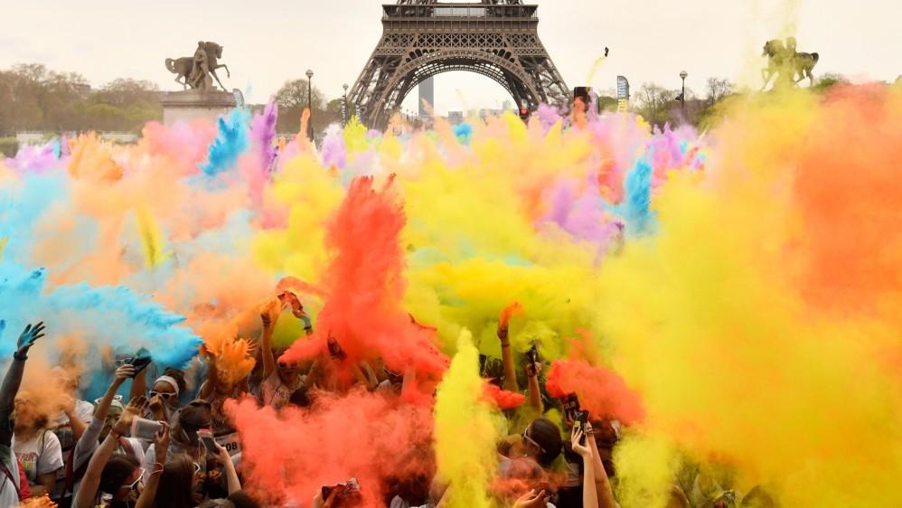 La gente arroja polvo de colores mientras celebran la finalización de sus cinco kilómetros en el Color Run 2018. Foto: CHRISTOPHE SIMON