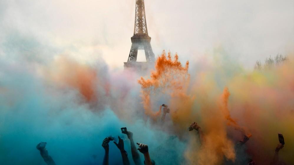 La gente celebra al final de la carrera Color Run 2018 frente a la Torre Eiffel en París. Foto: CHRISTOPHE SIMON
