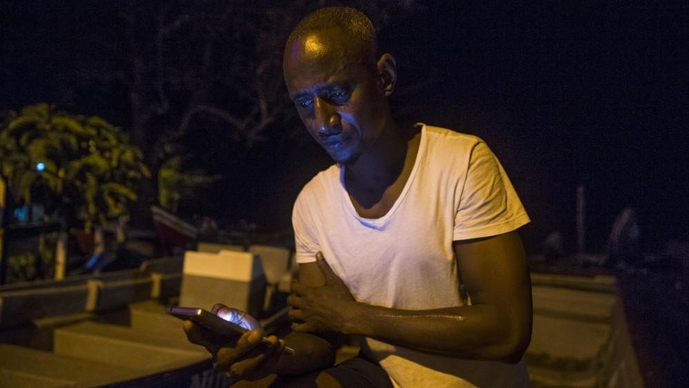 Ibrahim Muctar Jalloh de Sierra Leona lleva varios meses en Capurganá. Su única forma de comunicarse con la familia es a través de redes sociales en su celular. Pasó varios meses detenido en un campo de refugiados en Panamá donde según él tuvo que cortarse el brazo izquierdo para que lo dejaran salir. Foto: Esteban Vanegas