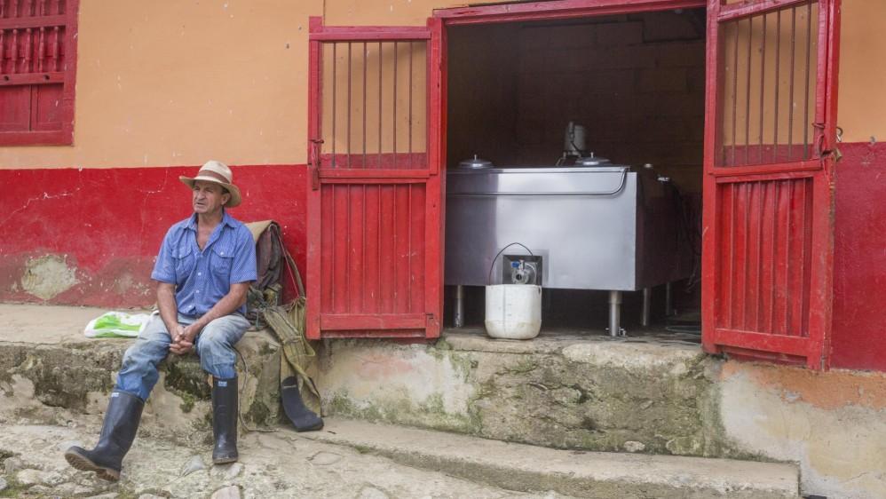 Gustavo Elías Mazo en su finca del municipio de Belmira. Atrás, el tanque de enfriamiento en el que se almacena la leche. Foto: Edwin Bustamante